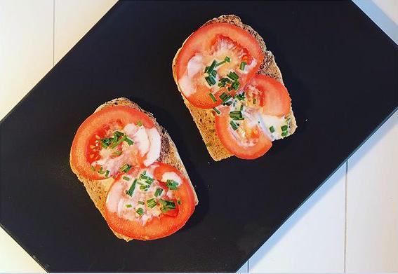 Feine Tomatenbrötli mit Schnittlauch auf einem schwarzen Teller serviert