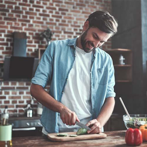 Mann in der Küche am Gemüse schneiden